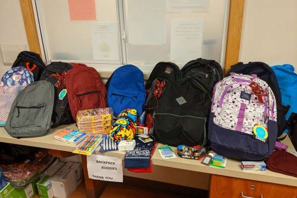 A countertop full of backpacks and other donations.