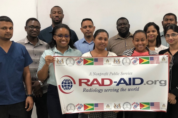 The radiology residents of Georgetown Public Hospital hold a RAD-AID International banner.