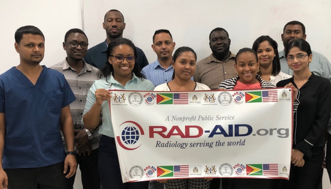 The residents of Georgetown Public Hospital hold a RAD-AID International banner.