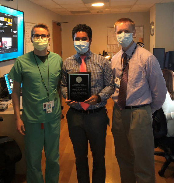 Doctor Joseph Grajo poses with Chief Residents Jerry Slater and Eric Pepin while receiving plaque