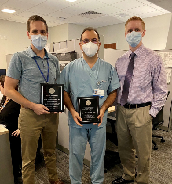 Doctor Ibrahim Tuna poses with Chief Residents Orrin Dayton and Eric Pepin while receiving plaque